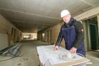 Haustechniker Michael Lüdtke vor den Plänen für das neue Haus St. Martin. Foto: SMMP/Ulrich Bock