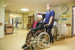Warten vor dem Aufzug: Renate Weiß begibt sich mit Altenpflegehelfer Patrick Köster auf die Reise. Foto: SMMP/Ulrich Bock