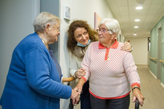 Maria Oreskou bringt Margarete Wirwalski in ihr Zimmer. Ihre Freundin Ingeborg Effenberg hat das Nachbarzimmer schon bezogen. Foto: SMMP/Ulrich Bock