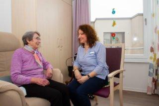 Betreuerin Maria Oreskou plaudert mit der Seniorin Renate Scherdel. Die 88-Jährige fühlte sich zunächst während der Kurzzeitpflege im Haus St. Martin so gut aufgenommen, dass für sie keine andere Einrichtung mehr infrage kam. Foto: SMMP/Ulrich Bock